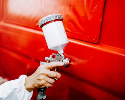 close up details of spray gun in automotive industry. painting a red car